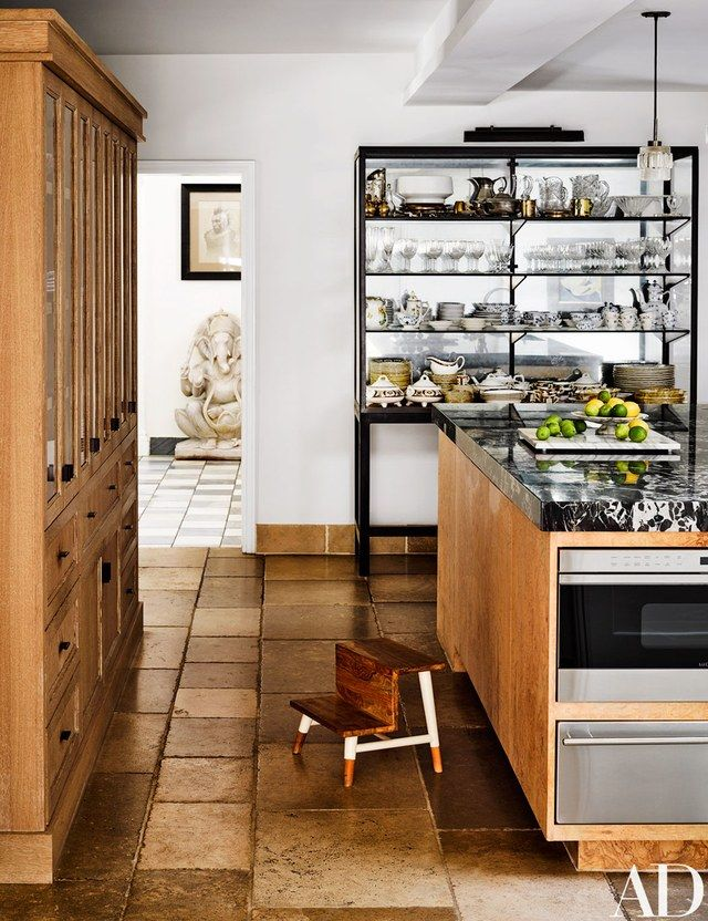 The burl-wood kitchen island features a marble top and a Wolf warming drawer and microwave.