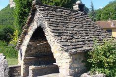 Un four à pain   -   Il ressemble à une minuscule chapelle.  Une voûte ouverte pour l'abri et l'abside,  four proprement dit. Le tout recouvert d'un  toit à deux pans.  La plupart sont encore en fonction et  sont célébrés au cours des fêtes traditionnelles.  Bugey.  France