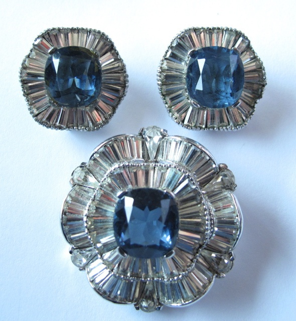 """This magnificent """"real look"""" diamond and faux sapphire pin and earrings are from my personal collection. All pieces are set in undulating or scalloped rhodium plated metal. All rhinestones are prong set and are bright and sparkly. There are no dead stones. The set is in excellent condition. Signed Jomaz. Circa 1950. Pin is 1 ½"""". Earrings are 1"""". Matches #2473 on this site. #161"""
