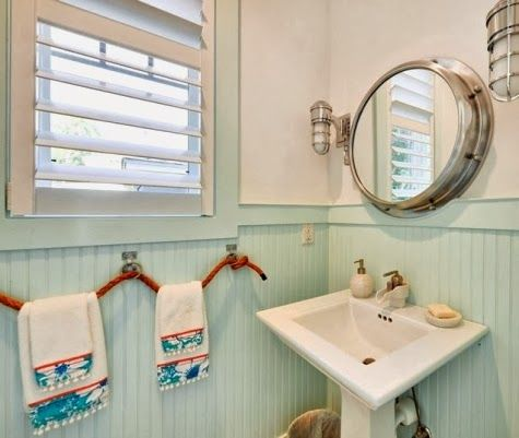 Nautical bathroom with porthole mirror and rope towel holder.