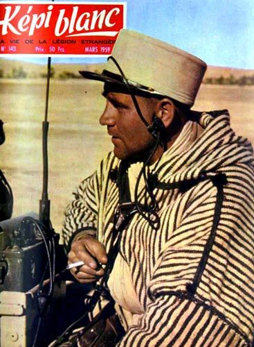 The March 1959 Képi blanc magazine cover showing a legionnaire (radio operator) of 4e CSPL dressed in a Djellaba and wearing a khaki-covered képi (designated for military operations outside the home base).