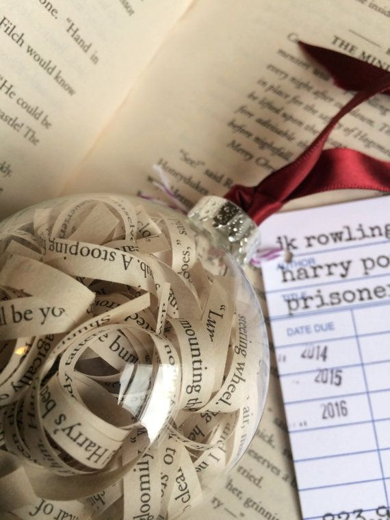 One glass ornament, perfect for any occasion or everyday display, filled with curled strips of sentences, upcycled from a used copy of Harry Potter and the Prisoner of Azkaban! A great keepsake for any lover of literature. A natural burlap ribbon is tied at the top to hang the ornament or simply sit it on your shelf in its gift box.  Measures about 8 1/2 in. around.  On the outside of the gift box comes a library due date card with the books author and title, the books Dewey Decimal number…
