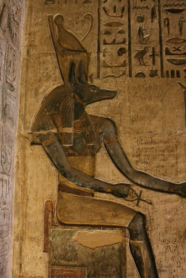 Relief depicting the jackal-headed god Anubis, seated and wearing 'Pschent', the Double Crown of Upper and Lower Egypt. Ptolemaic Period, ca. 305-30 BC. Ptolemaic temple of Hathor and Ma'at at Deir el-Medina.