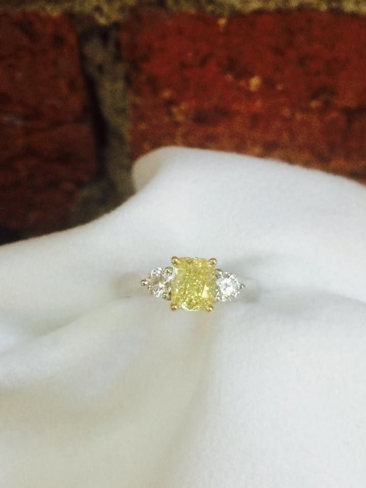 New addition to our yellow diamond collection: 1.38ct Australian Fancy Intense Yellow Cushion cut diamond set into a three stone ring accompanied by white diamonds on the side.