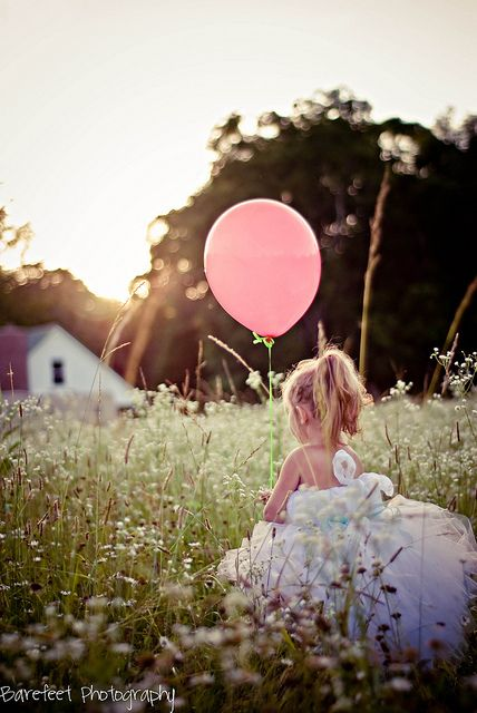 Little girl in field with balloon and pretty dress.