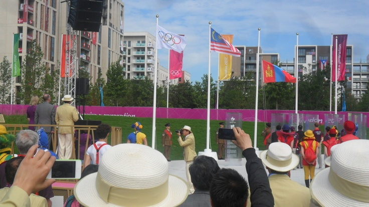 The Mongolian flag being raised at the Team Welcome Ceremony, Dep Chef de Mission on Podium with Olympic Village mayor, Sir Charles Allen.