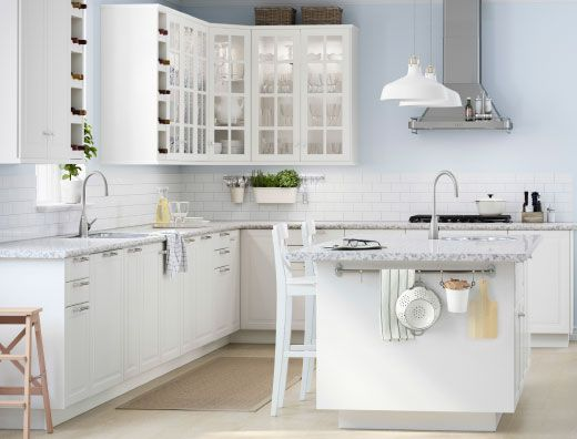 A large white kitchen with a lot of drawers, wall cabinets and a kitchen island.
