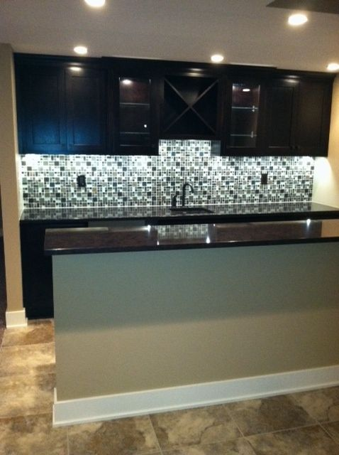 basement bar. I like the top cabinets, the dark stain and the layout with the sink in the middle...also the backsplash
