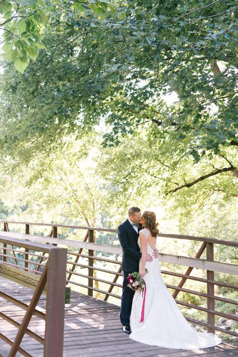 Bride and groom kiss on bridge in picturesque park setting
