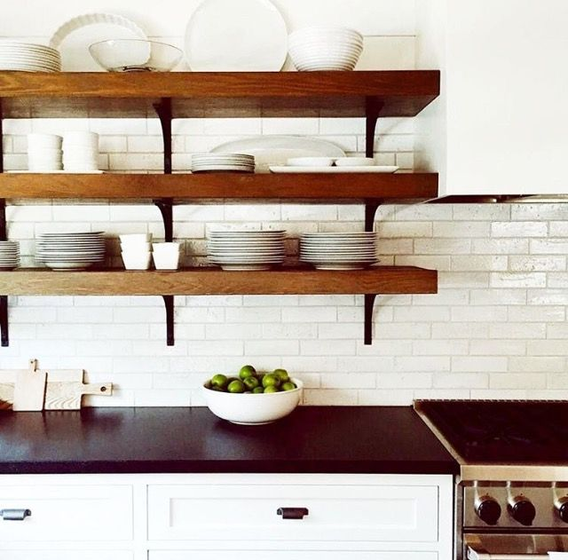 We've been #flirting with color all week, but a classic black and white kitchen gets us every time! The mix of brick #subwaytile , warm wood, #openshelving and dark stone #countertops is modern but still timeless and never dates. We're sold. 😊image via @wtrwrks