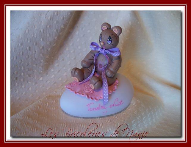 Caline, petite oursonne toute douce entièrement modelée à la main et en porcelaine froide, posée sur une veilleuse