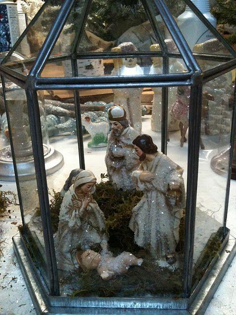 nativity scene displayed in a small terrarium or lantern.