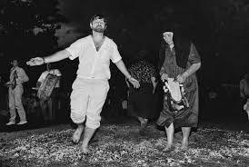 """-..Αναψε κόσμε τη φωτιά, να μπει ο Κωνσταντίνος. Ο Άγιος """"δείχνει το δρόμο"""" κι οι μύστες κρατώντας τις κωδωνοστολισμένες εικόνες ή τα ιερά αμανέτια μπαίνουν στ' αναμμένα κάρβουνα και χορεύουν. … – Στάχτ' να γέν'… Στάχτ' να γέν' … Στάχτ' να γέν'… Με τα γυμνά τους πόδια οι Αναστενάρηδες σβήνουν τα κάρβουνα και μέσα στη μαύρη στάχτη δεσμεύουν την αρρώστια, την επιζωοτοκία, την κακή τύχη. «Πατρογονικό το πάτημα στη φωτιά. Διαθήκ' του Αγίου!» http://www.youtube.com/watch?v=1MhGITKz2tA&sns=em"""
