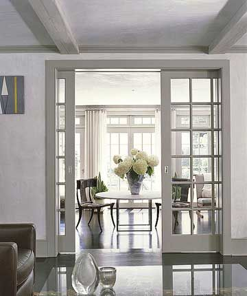Paned-glass Pocket Doors  What's more convenient than doors that disappear when you don't need them? That's the beauty of pocket doors. These paned-glass interior doors mimic the home's exterior windows. Leading from the living room, the pocket doors open on to an airy sunroom with casual dining and sitting space.