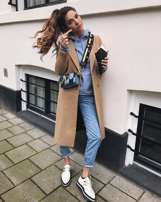 Negin Mirsalehi wears a beige overcoat with a pale blue hoodie and jeans combo. She completes this spring style with black-soled white brogues, and a funky cross body mini bag. Brands not specified.