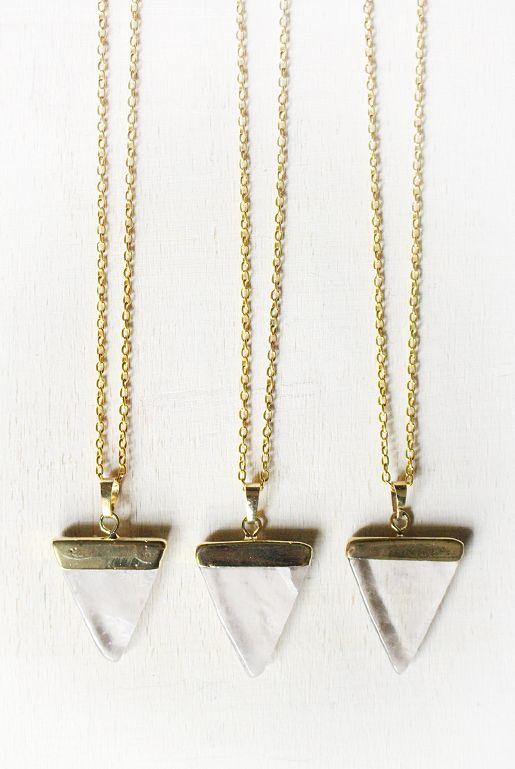 Guldpläterat halsband med en triangelformad berlock av bergskristall. | Gold plated necklace with a triangle-shaped quartz pendant.