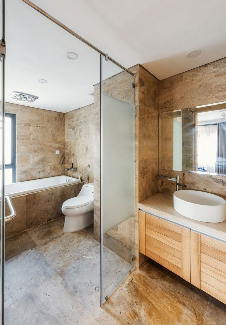 Apartment: Interesting ML Apartment in Hanoi, Vietnam Designed by Le Studio, Elegant Bathroom from ML Apartment showing Textured Brown Wall and Floor Tile and Tub Shower and Wooden Vanity and Oval White Vessel Sink and Frameless Mirror by Le Studio