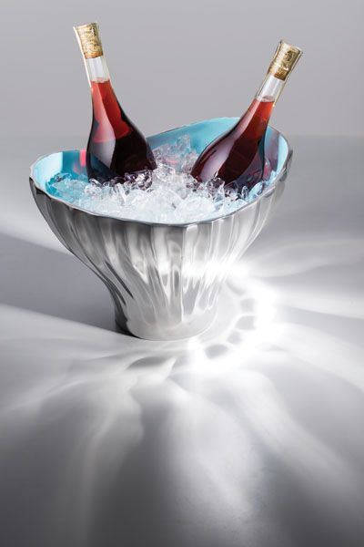 The Aquos Champagne Holder | Water takes on varied forms and creates many habitats. The AQUOS COLLECTION strives to express its many interpretations, from the ripples of undulating circles to placid and mirror-like surfaces to the scales of a fish. Shop this beautiful polished silver Nima Oberoi Lunares wine and champagne ice bucket.