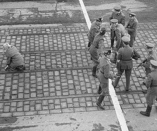 Police officers from West and East Berlin meet at a line marking the border in 1955. Try to understand how absurd the situation in this photo is.