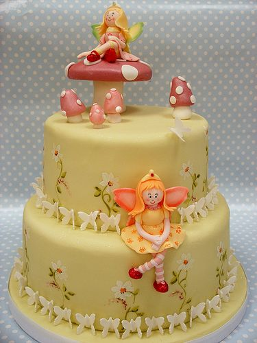 https://flic.kr/p/63Q667   Fairy Cake   This was a vanilla cake with vanilla buttercream and strawberry jam filling covered in fondant. Decorated with sugarpaste fairies and butterflies and hand painted daisies. This was for a friends daughter who requested two fairies, one pink and one yellow!