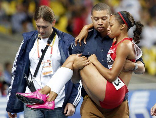 REFILE - ADDING IDENTITY OF MAN CARRYING FELIX Allyson Felix of the U.S. is carried off the track by her brother Wes Felix after suffering an injury in the women's 200 metres final during the IAAF World Athletics Championships at the Luzhniki stadium in Moscow August 16, 2013. REUTERS/Maxim Shemetov (RUSSIA - Tags: SPORT ATHLETICS)
