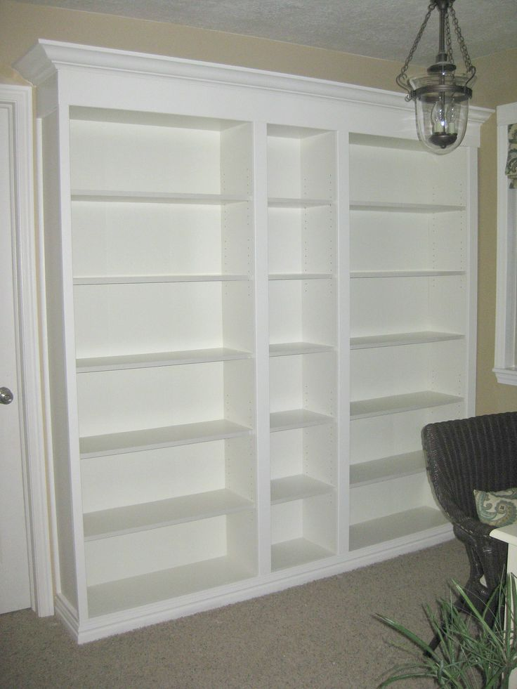 DIY built ins with bookshelves and mold trimming at top makes it look like expensive built in shelves