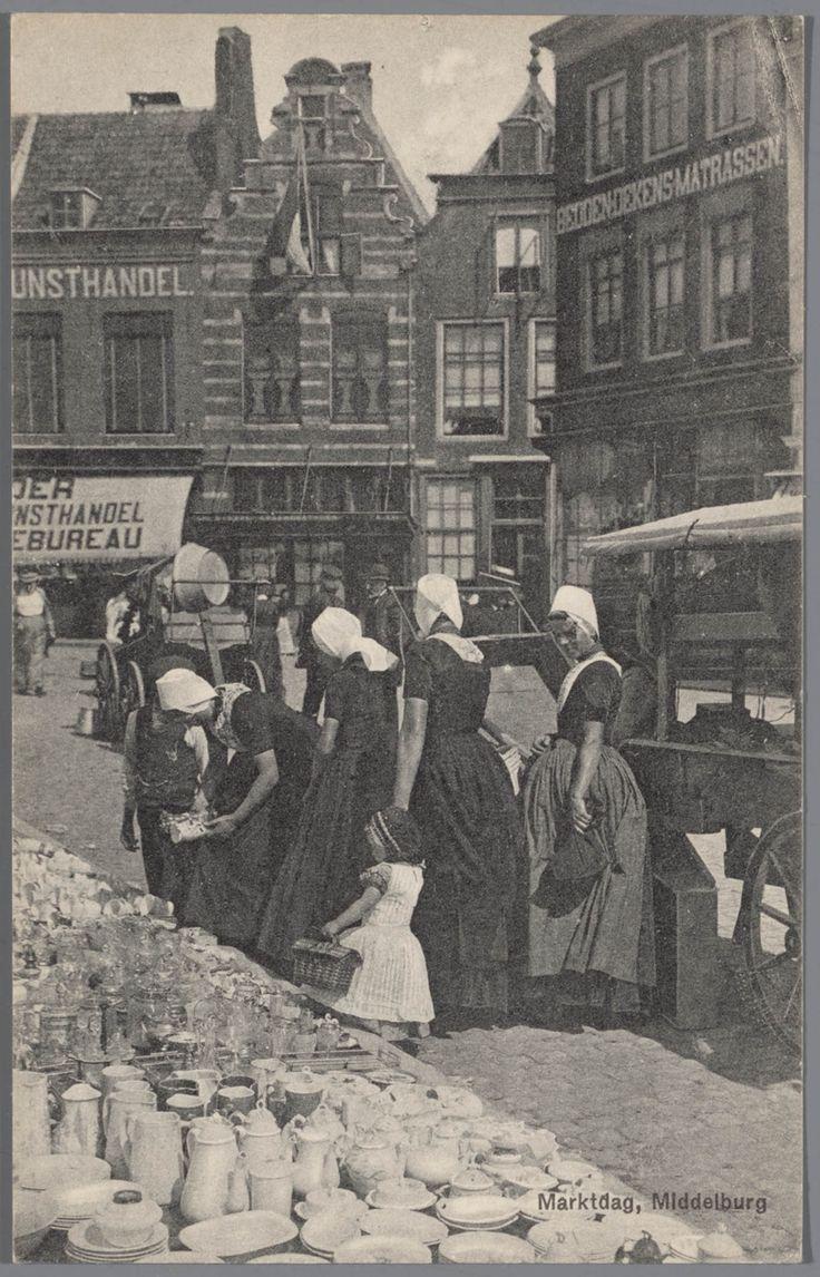 Vrouwen in Walcherse streekdracht op de markt te Middelburg. Het kleine meisje vooraan draagt nog een gehaakt mutsje over haar ondermuts en een jurkje met hoge schort. Als ze een jaar of 6 is wordt ze 'in het jak' gekleed en is dan een verkleinde versie van haar moeder. 1905-1972.
