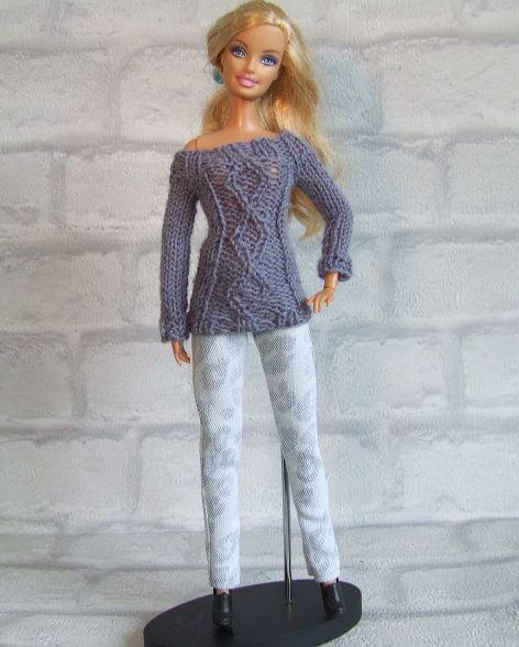 Gebreide grijze trui met ingebreid ruitmotief op jeans met panterprint. De trui…