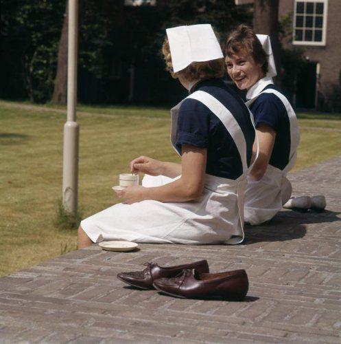 Ton Nelissen | Twee verpleegsters/zusters in uniform drinken, buiten zittend op een muurtje, koffie. Ze hebben hun schoenen uitgedaan, Nederland, 1964.
