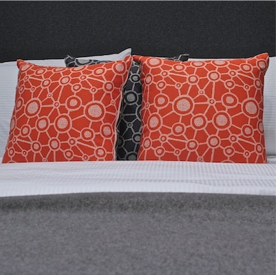 Bold orange cushion with grey back in a joined spot pattern