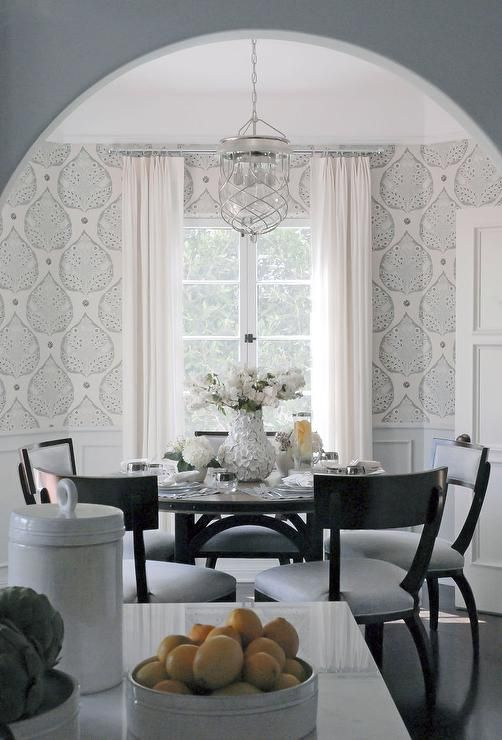 Classically beautiful dining room features an dark wood round dining table surrounded by black klismos dining chairs fitted with light gray cushions illuminated by a caged glass lantern.