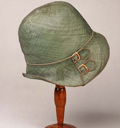 A pale green straw cloche with contrast trim and metal buckle details on the…