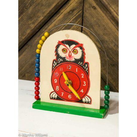 Pöllö, jossa on kello vatsassa  ja helmitaulu ympärillä. Valmistaja mahdollisest Brio.