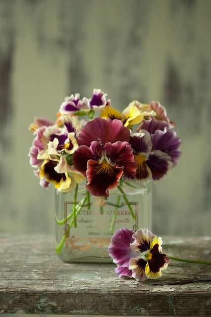 Pansies in a perfume bottle.