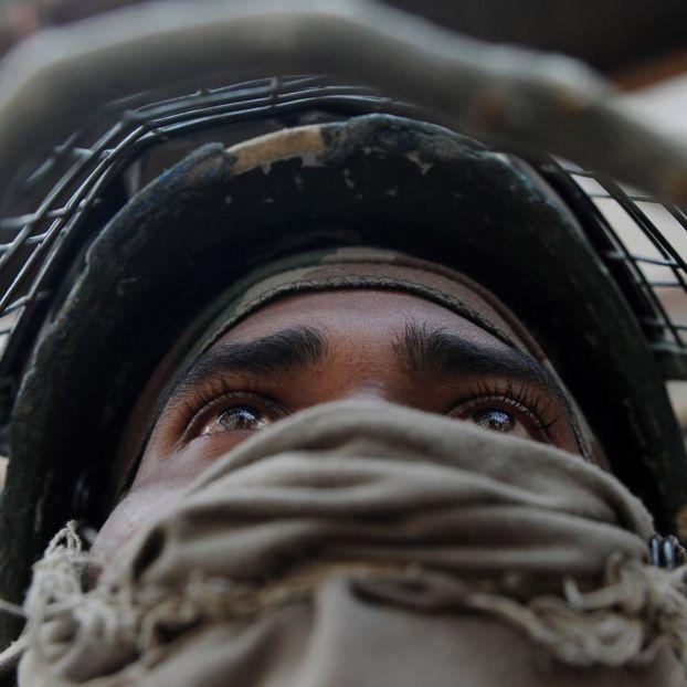 Un paramilitare indiano pattuglia l'area di Batmaloo a Srinagar, nel Kashmir
