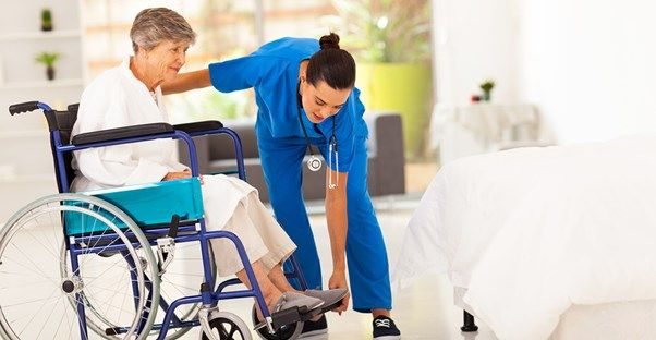 An elderly woman being assisted at a senior care center