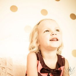 Girl sitting on her bed in her bedroom in front of golden polka dot wall stickers on a beige wall.
