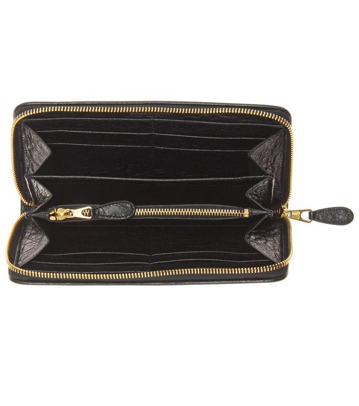 Entscheiden Sie sich mit diesem Portemonnaie von Balenciaga für ein elegantes Essential, an dem Sie lange Zeit Ihre Freude haben werden. Das schwarze Accessoire ist aus grob genarbtem Lammleder gearbeitet und mit einer dekorativen Lasche versehen. Reißverschluss und Logo-Schriftzug in Gold setzen luxuriöse Akzente.
