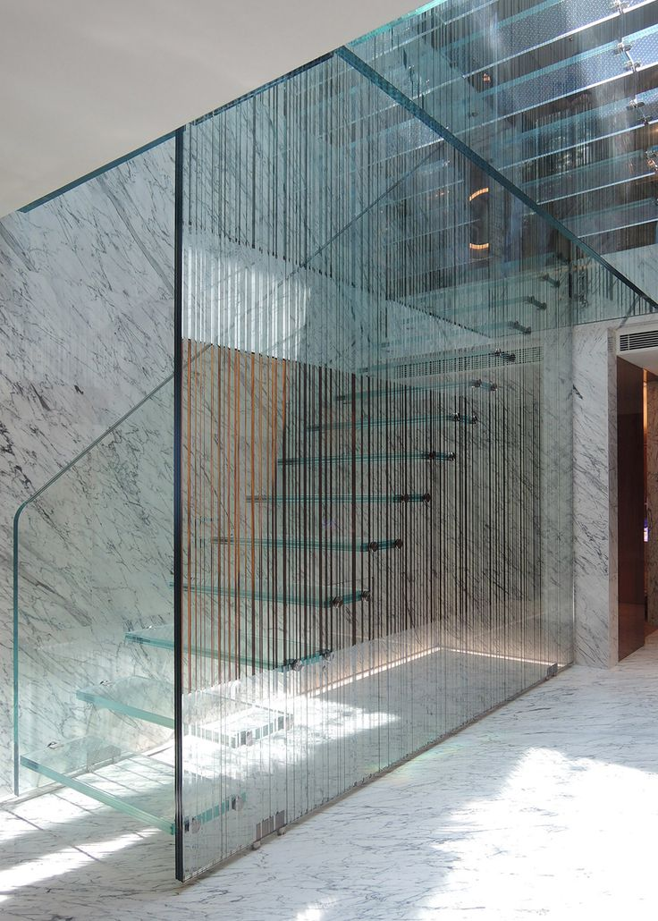 This patterned glass staircase forms the centrepiece of an apartment in Hong Kong