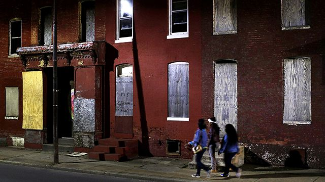 In this March 29, 2013 photo, women walk past blighted row houses in Baltimore. Baltimore is far from the worst American city for poverty, b...