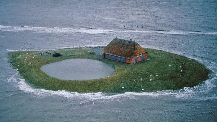 Hallig Habel, a farm in the flatlands of North Frisian Islands, Germany, during an extreme high tide. Handbuilt Shelter by Lloyd Kahn | Photo credit: Hans Joachim Kürtz from Home Work