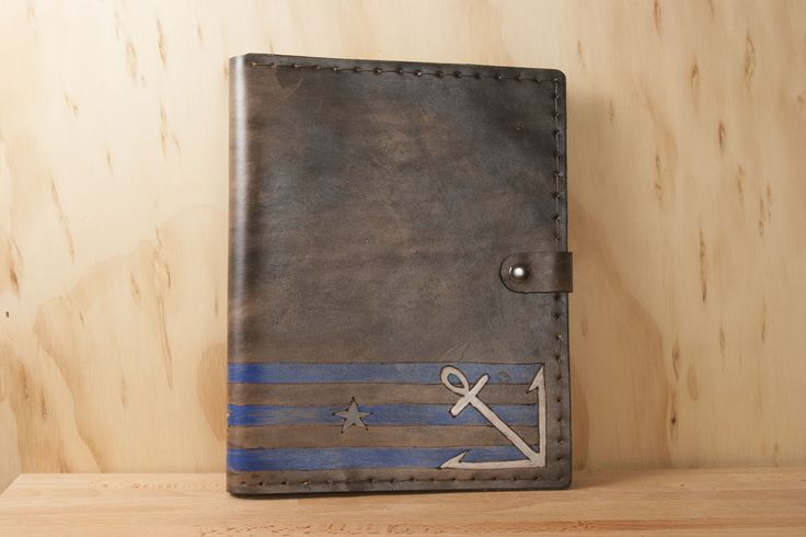 Protect your tablet with a handmade leather iPad or Kindle case in the Stu pattern.  This leather tablet case has the nautical trifecta along the bottom - stars, stripes and an anchor. It opens like a portfolio to reveal a silicone insert to securely hold your iPad or Kindle in place.