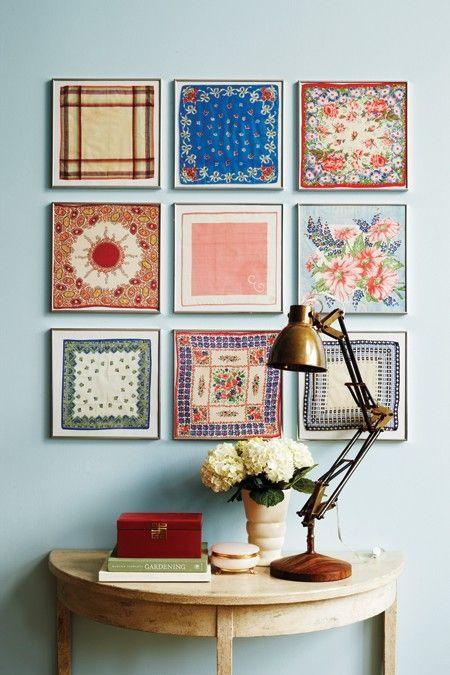 aparador em madeira com vaso de flor, livros, luminária vintage e quadros com retalhos de tecido na parede: