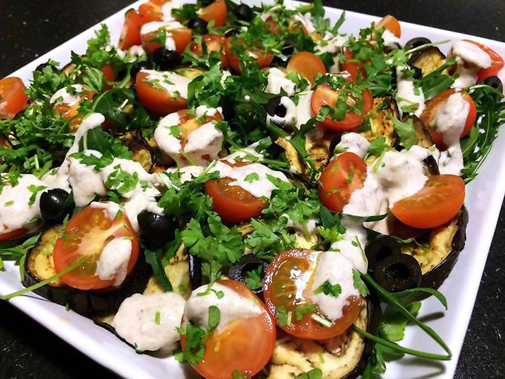 Bagt aubergine salat med cherrytomat, rucola og cremet tahin og yoghurt dressing.