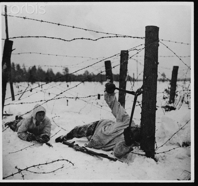 Soldier Cuts Wire on Finno-Russian Front 1940 - A Finnish wire-cutter goes into action on the snow covered Finno-Russian front during the Second World War.