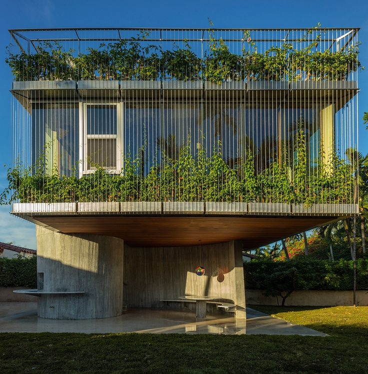 This plant-covered extension to a bungalow in Miami is supported by a spiral concrete core that matches the sun's path to provide maximum daylight.