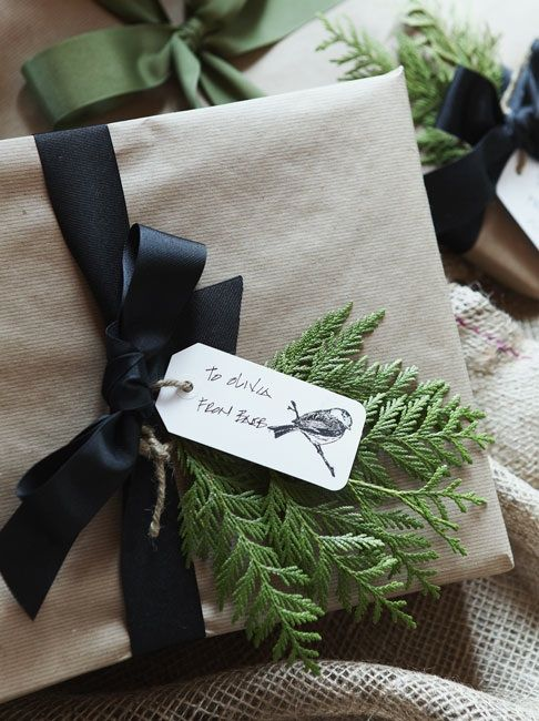 holiday gift wrapping: neutral paper, black ribbon, evergreen and tag