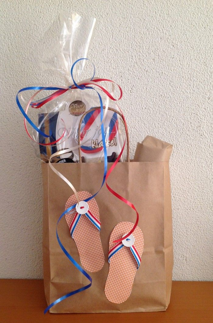 Geslaagd! Rood-wit-blauw-oranje. Relaxpakket (tijdschrift, koekje, etc.) Bruine papieren draagtas/kadotas versierd met teenslippers gemaakt met papier, lint en knopen.
