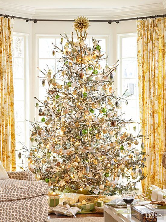 "When you love a specific color scheme, your decorating philosophy can be ""the more the merrier."" Pretty twinkling lights, shiny gold and green ornaments, and kid-friendly DIY garland are finished off with a sprinkling of artificial snow. A unique and eye-catching tree topper is the perfect final touch.   Editor's Lighting Tip: Thin out branches before decorating to make each light and ornament have more presence. /"