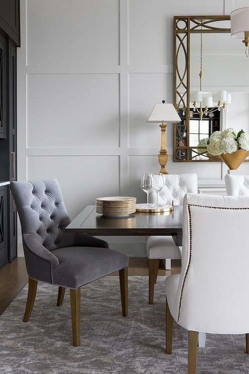 Wonderfully styled white and gray dining room boasts a gold trellis mirror hung from a board and batten wall above a white buffet cabinet lit by gold lamps.